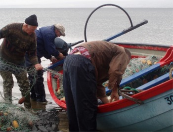 Pat McDonald, gets some help gathering his drift net for the last time. Photo courtesy BBC.